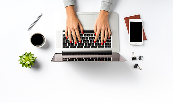 Woman's hands typing on a laptop