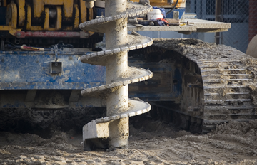 Excavator drilling a hole in the ground