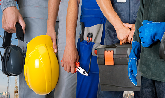 Construction workers waist down holding equipment