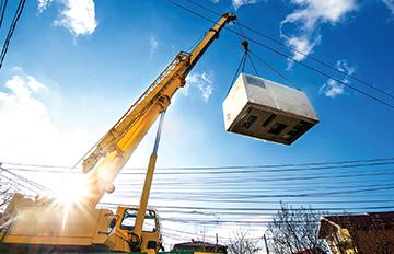 Yellow crane lifting electric generator