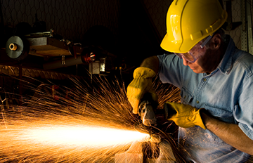 Man wearing protective equipment using a grinder