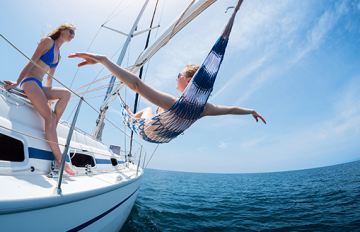 Woman with open arms lying on a boat hammock