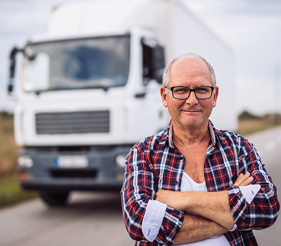 Man with crossed arms standing in front of a truck