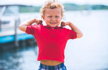 Smiling child flexing arm muscles
