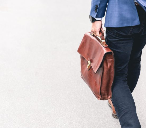 Business person carrying brown briefcase