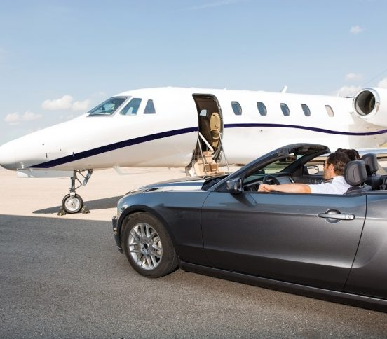 Grounded aeroplane and man driving convertible car