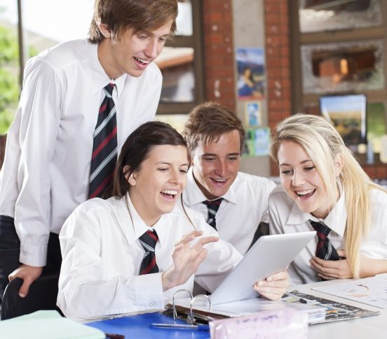 School students laughing while looking at a tablet