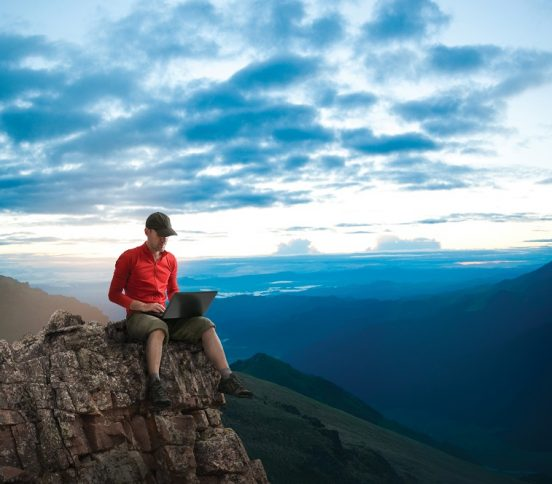Man sitting on a mountain with a laptop