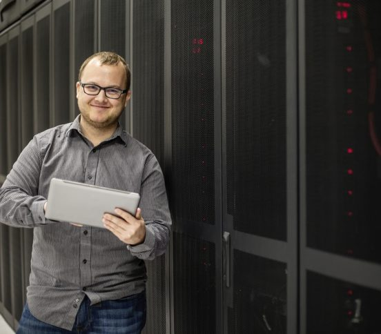 Man holding tablet next to IT infrastructure